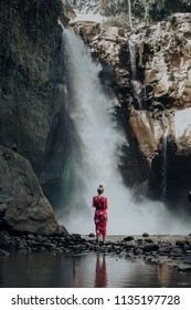 Young woman in red dress standing at Bali waterfall