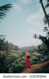 Young woman in red dress standing at Bali Rice Terrace