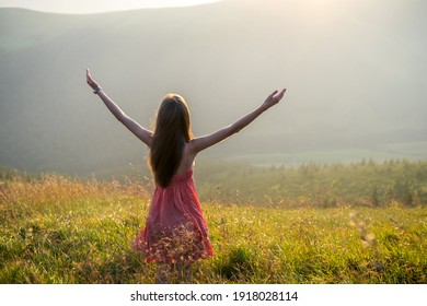 Young woman in red dress standing on grassy meadow on a windy evening in autumn mountains raising up her hands enjoying view of nature.