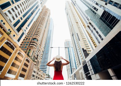 Young woman in red dress and straw hat walking near skycrapers in modern city. Low angle view