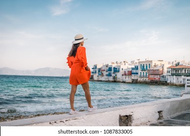 Young woman in red dress at the Streets of old town Mikonos, Little Venice Mykonos Greece