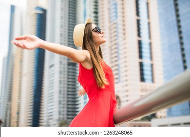 Young woman in red dress, sunglasses and straw hat with raised hands enjoy the view on downtown skycrapers.
