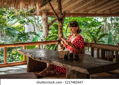 Young woman in red dress using smartphone in the jungle cafe. Bali island. Indonesia.