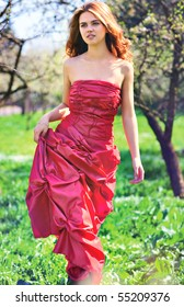 Young woman in red dress walking in garden.