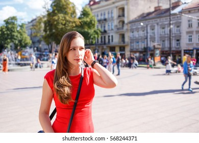 Young woman in red dress walking on street on sunny summer day