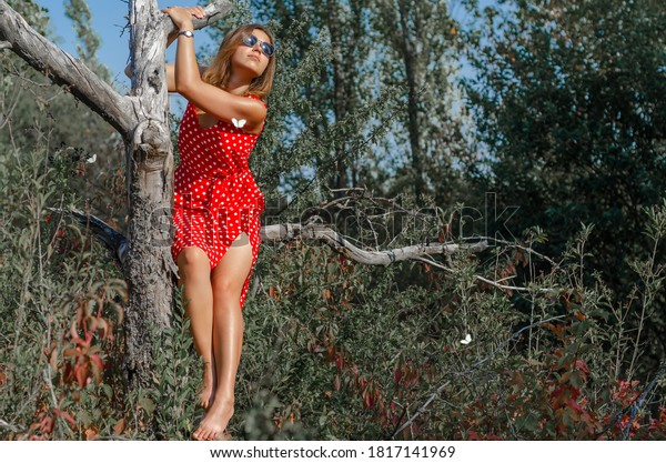 Young woman in a red dress in white polka dots sitting on a branch of dry tree in an abandoned garden