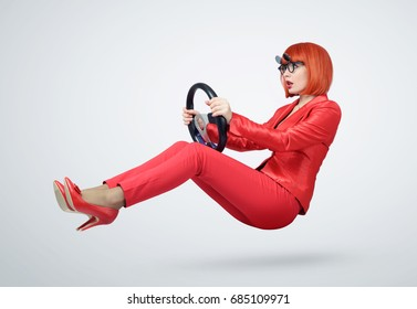 Young woman in red driver car with a steering wheel, auto concept