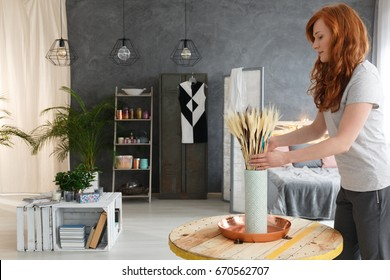 Young woman with red hair decorating contemporary fancy industrial apartment
