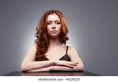 Young woman with red hair portrait. On gray wall background.