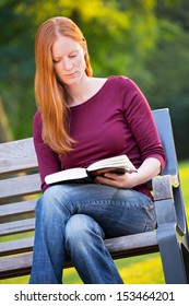 A young woman with red hair reading a book on a bench in a park.