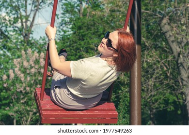 Young woman with red hair in sunglasses smiles swinging on a swing in a city park. The woman on the swing turned around while moving. Childrens entertainment for adults