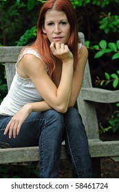 Young woman with red hair and white blouse sitting on bench - leaning forward