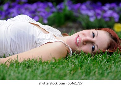 Young woman with red hair and white blouse laying in grass