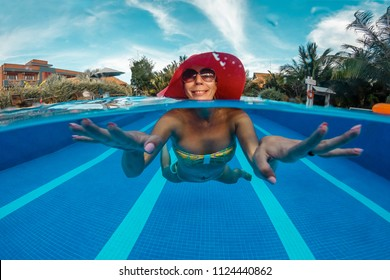 Young woman in red hat has a fun in swimming pool