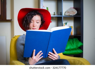 Young woman with red hat reading a book with blue cover