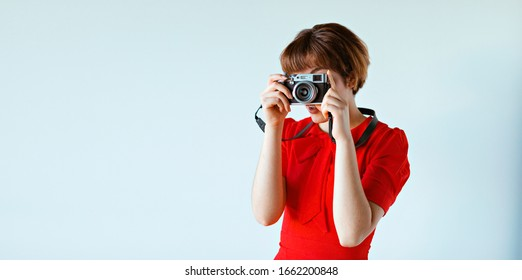 Young woman in red hipster dress takes photos