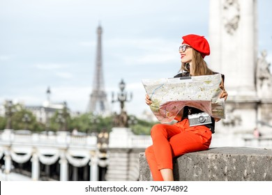 Young woman in red holding a tourist map sitting on the footbridge with Eiffel tower on the background in Paris