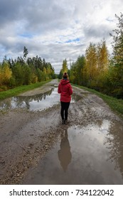 young woman in red jacket enjoying nature on dirt road with water puddles . Latvia