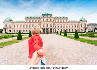 Young woman in a red jacket pulls her boyfriend by the hand against the background of the upper Belvedere in Vienna, Austria