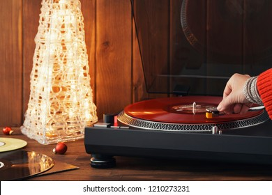 A young woman in a red knitted winter pullover puts a red vinyl record on a turntable, a stylus a needle and listens to music against the background of a glowing Christmas tree and a cozy New Year's