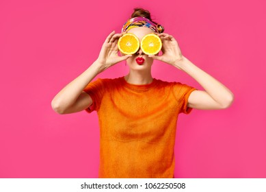 Young woman with red lips on vibrant pink background holds cut orange in her hands near eyes and kissing. Concept of healthy food and lifestyle