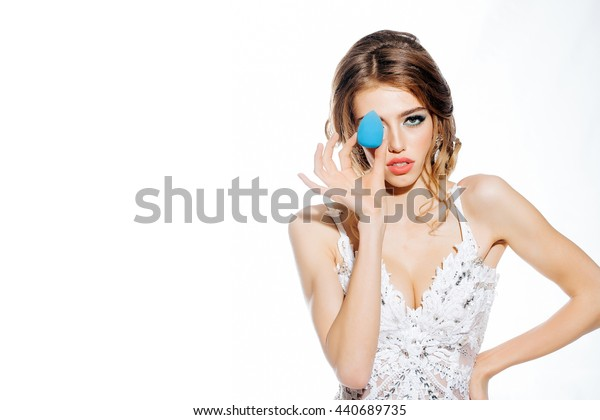 Young woman with red lips on pretty face in elegant dress holding makeup sponge in studio isolated on white background, copy space
