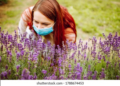 Young woman with red long hair wearing surgical mask trying to smell flowers of purple lavender. Allergy, covid, flu.
