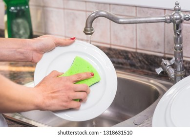 Young woman with red manicure, washing dishes in the sink of the kitchen .