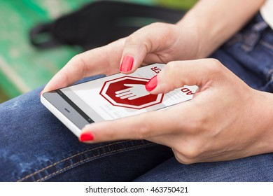 Young woman with red nails holding and using smart phone outdoors with ad blocker screen