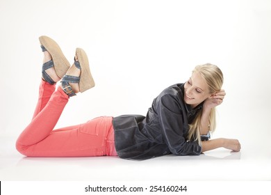 young woman in red pants lies smiling on ground