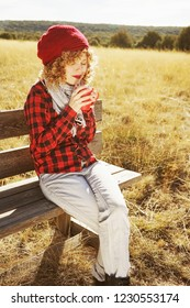 A young woman in red plaid shirt with a wool cap and scarf taking a cup of tea or coffee while she is sunbathing sitting in a wooden bench in a yellow field with backlight from autumn sun
