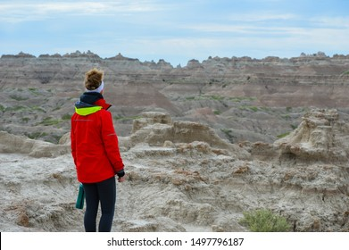 Young woman in a red raincoat stares off into the Badlands scenery with her back to the camera