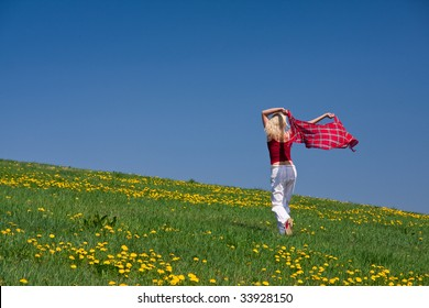 young woman with a red scarf on a meadow in the springtime