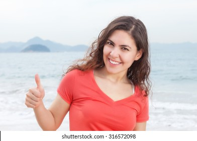 Young woman in a red shirt at beach showing thumb