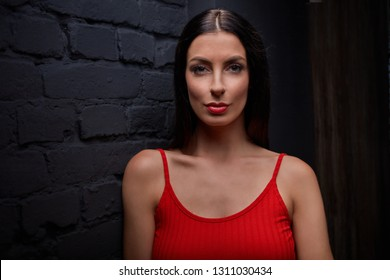 Young woman in red smiling against black wall, portrait.