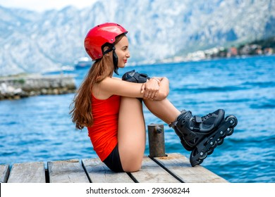 Young woman in red sportswear with skating rollers sitting on the wooden pier near the sea