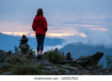 Young woman in red stands near the cairns and looks into the valley at sunset. Altai Republic, Russia. Image has some noise