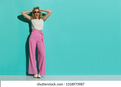 Young woman in red striped wide leg trousers and sneakers is holding head in hands and shouting. Full length studio shot on turquoise background.