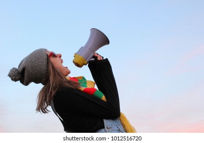 Young woman in red sunglasses shouting in the megaphone. Hipster girl shouting in the megaphone.