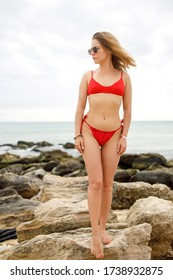 Young woman in red swimsuit standing on stones