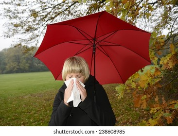 Young woman with red umbrella blowing nose,cold,flu allergie