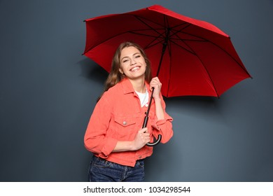 Young woman with red umbrella on color background