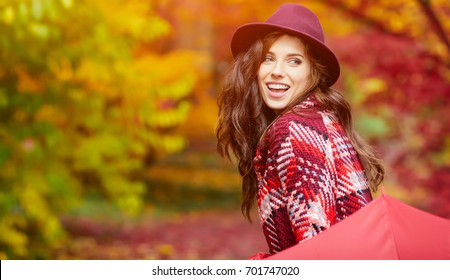 Young woman with red umbrella walking on autumn city park. Beautiful fall time in nature