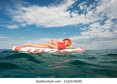 young woman in red wetsuit lay down on SUP board and having sunbathe