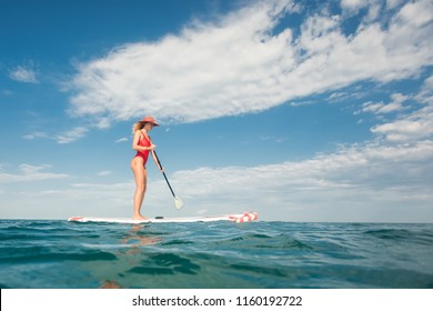 young woman in red wetsuit riding SUP board