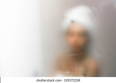 Young woman reflected in the mirror blurred by the steam. Defocused blurry background.