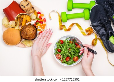 Young woman refuses to eat junk food and makes choice to do exercises and eat healthy meal. Preparing a body for vacation time in summer. Copy space