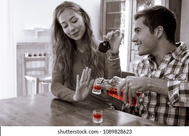 young woman refuses liquor drinking she has car keys in hand. responsible drinking and diving concept. black and white image with colorful liquor highlighting.