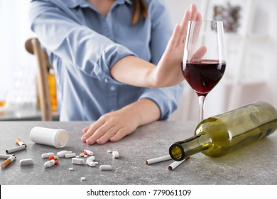 Young woman refusing glass of wine while sitting at table