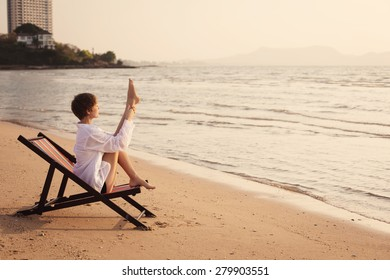 young woman is relax and doing fitness exercise on the beach at sunset